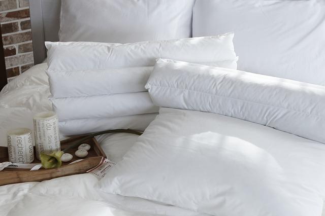postel s bílými polštáři